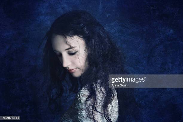 Pale young woman with tousled long dark hair looks down sadly, textured dark blue background, studio shot