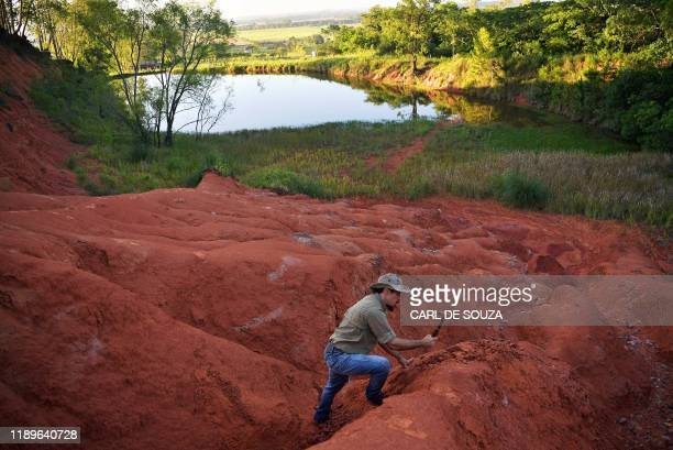 Paleontologist Jose Darival Ferreira digs at an excavation site in Agudo, Brazil, on December 3, 2019. - In 2014, the paleontology team at CAPPA...