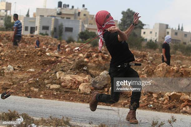 Palesitinan youth uses a slingshot to hurl stones toward Israeli soldiers during clashes following a protest against the expropriation of Palestinian...