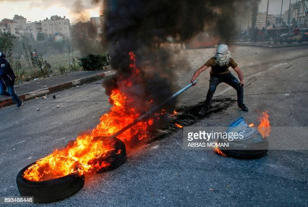 Palestian protester uses a stick to move flaming tires during clashes with Israeli security forces near the West Bank checkpoint of Qalandia on the...