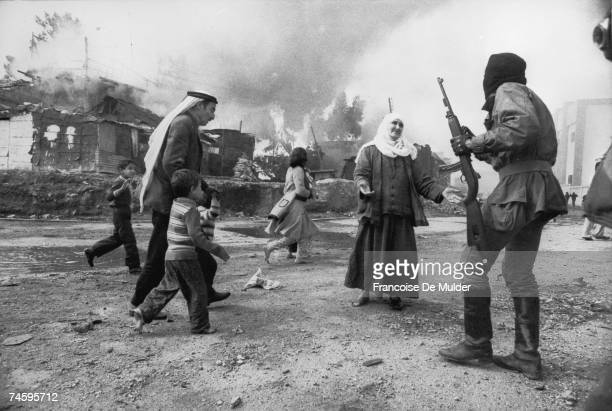 A Palestinain woman pleads with Christian militia in Beirut while a man tries to take children to safety during the Lebanese civil war 19th January...