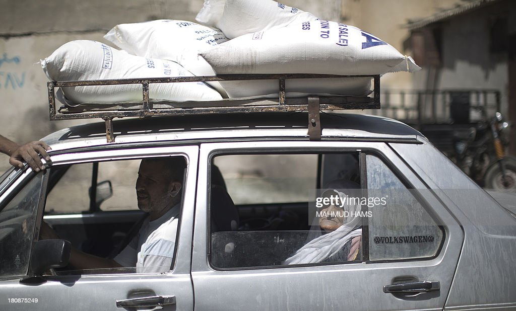 A Palestinain woman sits inside a car loaded with bags of wheat flour distributed at an aid distribution centre of the United Nations Relief and Works Agency (UNRWA) in Gaza City on September 17, 2013. UNRWA operates through 11,000 staff in over 200 installations across the Gaza Strip, providing education, health care and social services to Palestinian refugees.