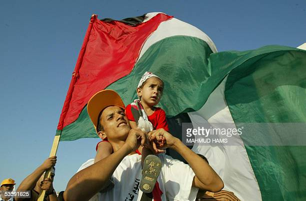 Palestinain youth carries his sister during a celebration rally in Gaza city 15 August 2005 as Israel began its historic pull out operation from the...
