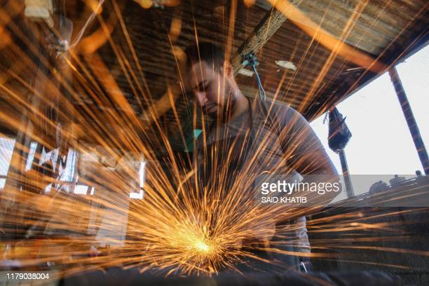 Palestinan bladesmith Saif Abu Adira works on one of his creations in his workshop on the roof of his house in Khan Younis on southern Gaza Strip on...