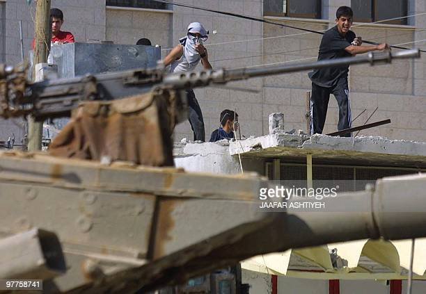 Palestinan youths stones at an Israeli tank in the West Bank city of Nablus 03 June 2003 Israeli Prime Minister Ariel Sharon and his Palestinian...