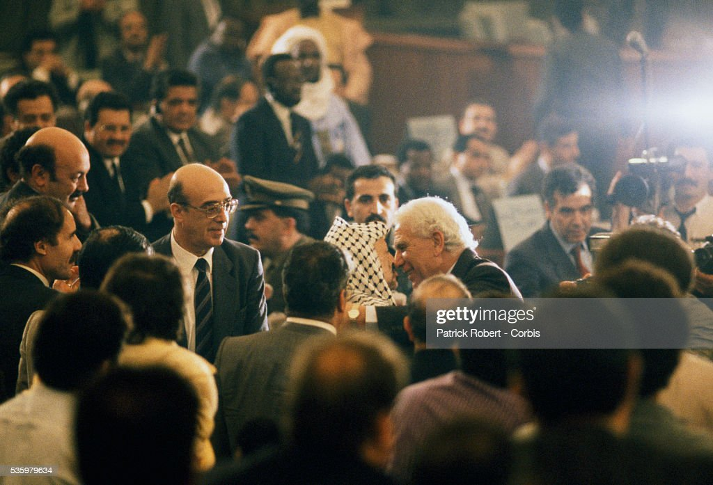 Palestine Liberation Organization leader Yasser Arafat greets Algerian President Chadli Bendjedid at the 19th session of the Palestinian National Council. The PLO proclaimed the state of Palestine, acknowledged resolutions 181, 242, and 338, and condemned terrorism during the meeting.