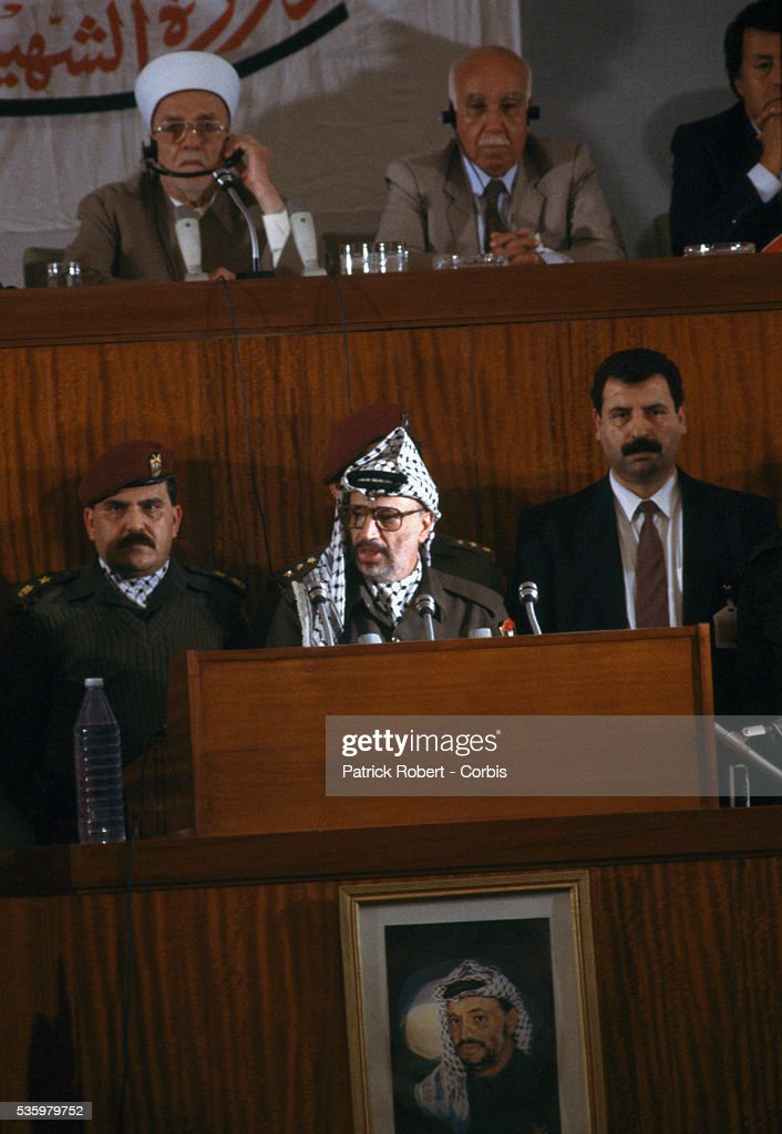 Palestine Liberation Organization leader Yasser Arafat speaks at the Palestinian National Council. The PLO proclaimed the state of Palestine, acknowledged resolutions 181, 242, and 338, and condemned terrorism during the meeting. Behind Arafat on the top left is Sheikh Abdel Hamid As-Sayeh, President of the Palestinian National Council.