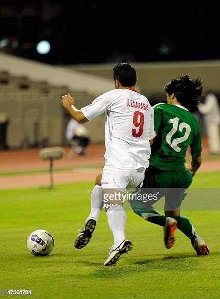 Palestine's Ahmed Hassan Zaatara vies for the ball against Saudi Arabia's Khalid alGhamdi during their Arab Cup football match in Saudi summer resort...