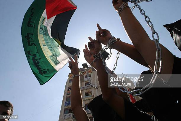 Palestiniains chain their hands in a symbolic gesture during a demonstration calling for the release of Palestinian prisoners held in Israeli jails...