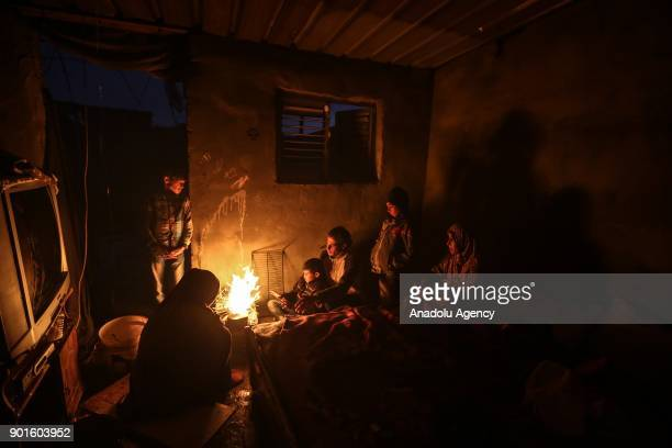 Palestinian Abu Shavish family members try to warm themselves around a fire inside their house without a door and windows as they live in hard...