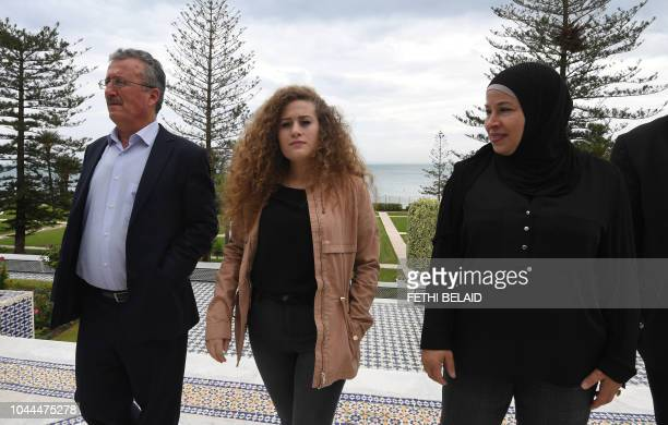 Palestinian activist Ahed Tamimi poses with her father Bassem and mother Nariman Tamimi for a picture at Carthage presidential Palace before her...