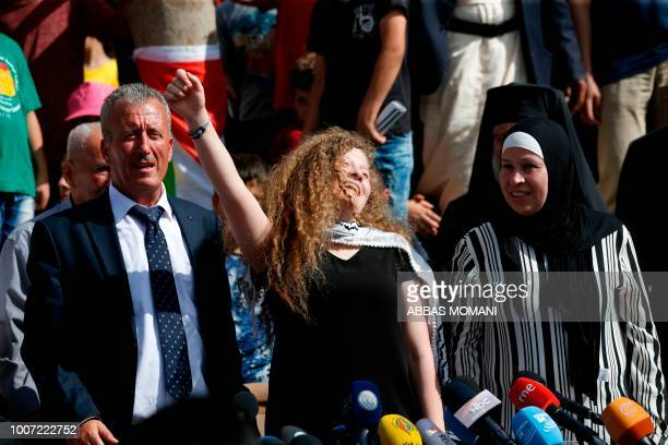Palestinian activist and campaigner Ahed Tamimi gestures as she stands between her father and mother during a press conference in the West Bank...