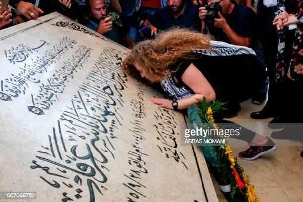 TOPSHOT Palestinian activist and campaigner Ahed Tamimi kisses the tombstone of former Palestinian leader Yasser Arafat at his mausoleum in Ramallah...