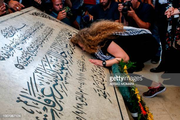 Palestinian activist and campaigner Ahed Tamimi kisses the tombstone of former Palestinian leader Yasser Arafat at his mausoleum in Ramallah in the...