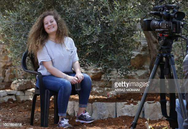 Palestinian activist and campaigner Ahed Tamimi smiles during an interview with Agence FrancePresse in the West Bank village of Nabi Saleh on July 30...