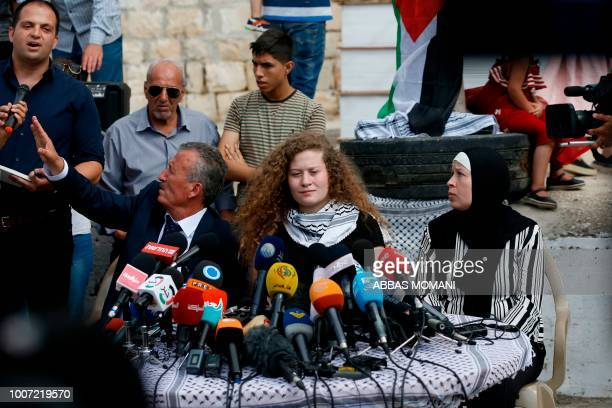 Palestinian activist and campaigner Ahed Tamimi speaks as she sits between her father and mother during a press conference in the West Bank village...