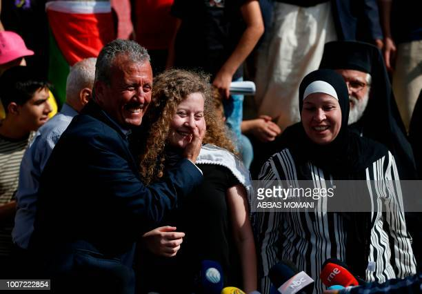 Palestinian activist and campaigner Ahed Tamimi stands between her father and mother during a press conference in the West Bank village of Nabi Saleh...