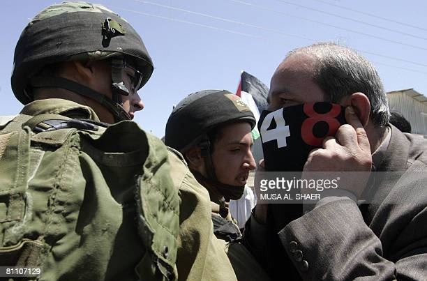 A Palestinian activist covers his face with a Tshirt celebrating Nakba as he argues with an Israeli soldier during a protest against Israel's...