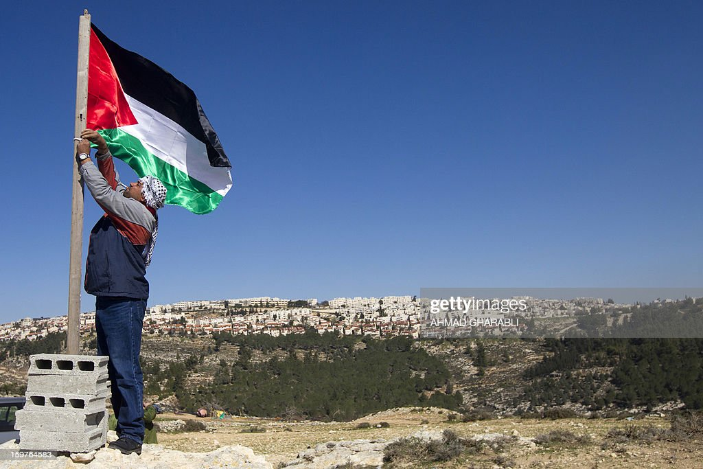 A Palestinian activist fixes a flag near the newly erected encampment set up to protest against Israel's intention to confiscate land on January 20, 2013 in the West Bank village of Beit Iksa. Activists say the Israeli army recently announced it would confiscate over 500 dunams (124 acres, 50 hectares) of land by the village, located on the northwestern outskirts of Jerusalem. On the background is seen the Israeli settlement of Ramot.