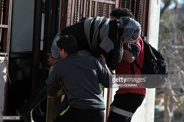 Palestinian activist Manal Tamimi is carried by friends into a house after she was shot in the leg with rubber bullets by Israeli border guards in...