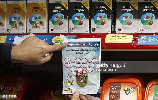 A Palestinian activist sticks a leaflet calling for the boycott of Israeli products to a shelf selling Israeli dairy products in a supermarket in the...