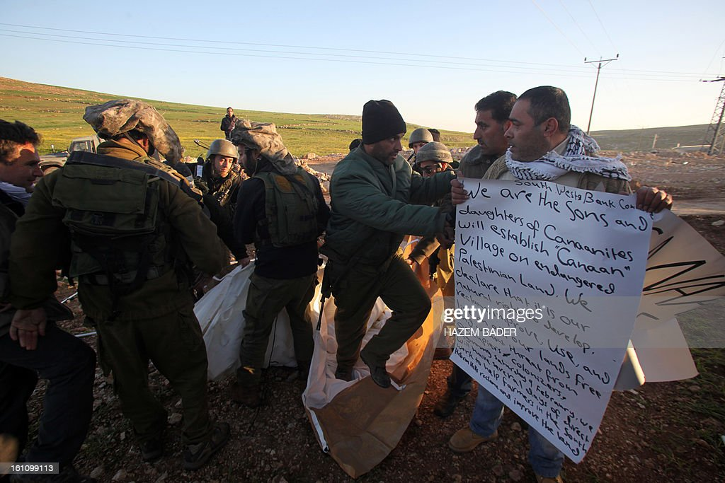 Palestinian activists are stopped by Israeli soldiers as they set up a new encampment to protest against settlement building in the Yatta, south of the West Bank city of Hebron on February 9, 2013. Soldiers dismantled tents that were being erected in two different areas near the town of Yatta, and forced activists to leave, the Palestinian witnesses said. BADER