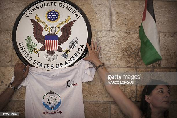 Palestinian activists hold a tshirt with the logo of the UN 194 campaign next to the emblem of the US General Consulate in east Jerusalem during a...