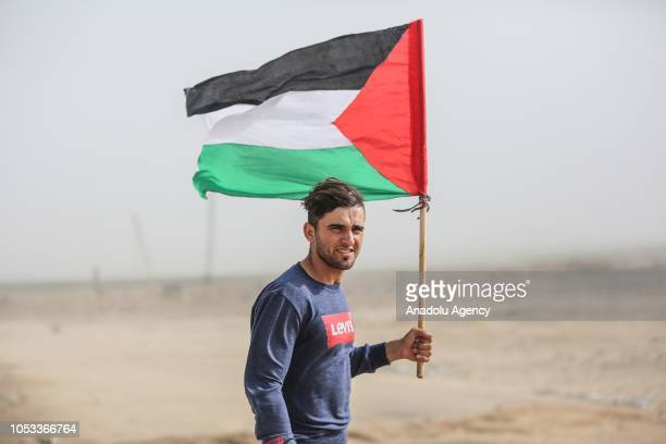 Palestinian Aed Abu Amro holds a Palestinian flag during an interview on his bare chested photograph which was captured by Turkey's Anadolu Agency's...