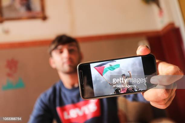 Palestinian Aed Abu Amro shows his bare chested photograph which was captured by Turkey's Anadolu Agency's photojournalist Mustafa Hassona holding a...