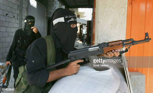 Palestinian Al Aqsa brigade militants take cover behind sand bag defensive positons from nearby Israeli forces within the Jabaliya refugee camp...