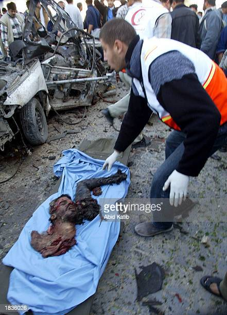 GRAPHIC CONTENT Palestinian ambulance worker collects parts of a bodyguard's body March 8 2003 in the Gaza Strip who is one of four palestinians...