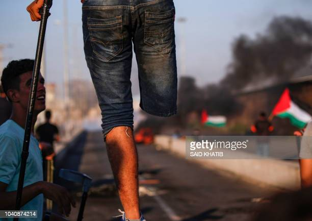 Palestinian amputee protester stands with a crutch on a concrete barricade while smoke plumes from burning tires billow in the background during...