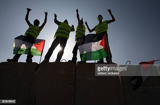 Palestinian and foreign activists flash the victory sign as they stand on top of a blast wall used by Israeli troops along Israel's controversial...