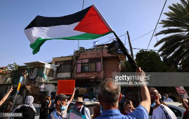 Palestinian and Israeli activists gather in front of Israeli settlers house during a demonstration against the expulsion of Palestinian families from...