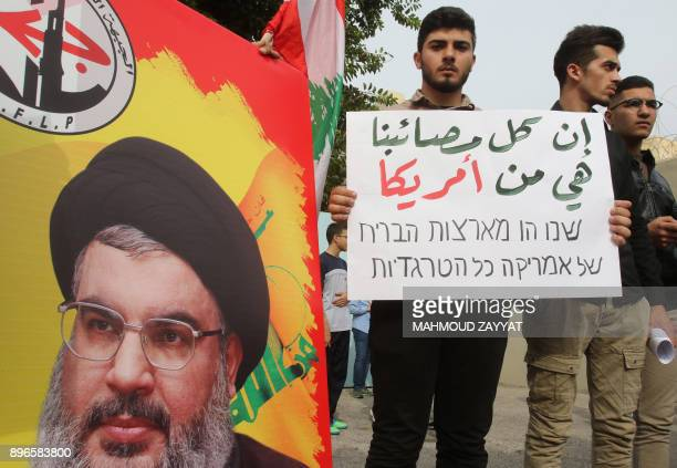 Palestinian and Lebanese hold a portrait of Shiite group Hezbollah chief Hassan Nasrallah during a protest in Lebanon's southern border town of...