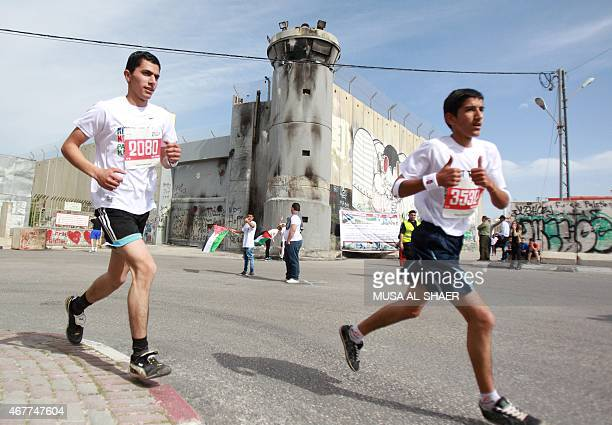 Palestinian Arab and foreign athletes run along Israel's controversial separation barrier as they take part in the Third Palestine Marathon in the...