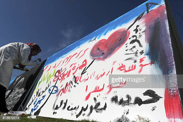 A Palestinian art student paints as she takes part in a festival marking the World Mental Health Day on October 11 2016 in Gaza City