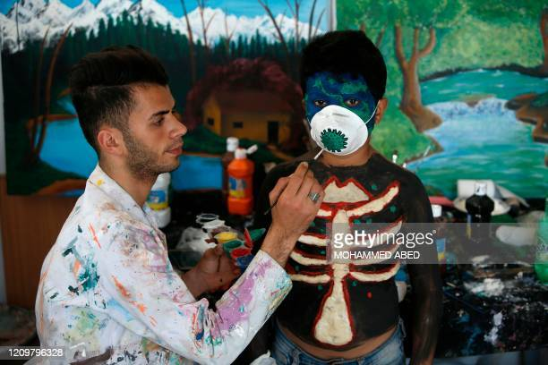 Palestinian artist Hammam Mosallam paints on a child's protective mask at his home workshop in the Nusseirat refugee camp in the central Gaza Strip...