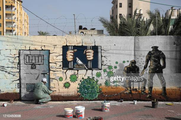 A Palestinian artist paints a depiction of the microscopic view of the coronavirus chained to a prisoner as part of a mural in support of...
