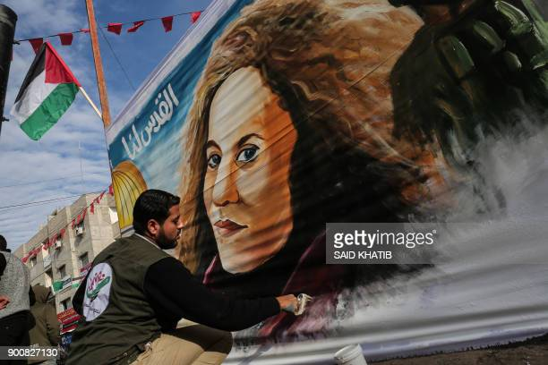 A Palestinian artist paints a portrait of Ahed Tamimi 16yearold prominent campaigner against Israel's occupation and who is currently detained on a...