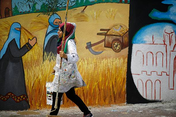 A Palestinian artist paints murals on the walls of a school run by ...
