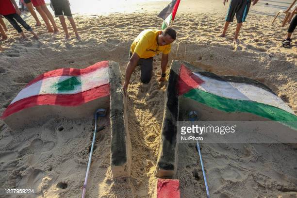 """Palestinian artist, paints the flag of Lebanon and Palestine on the sand sculpture titled """"Peace for Beirut"""", at the beach of Gaza city on..."""