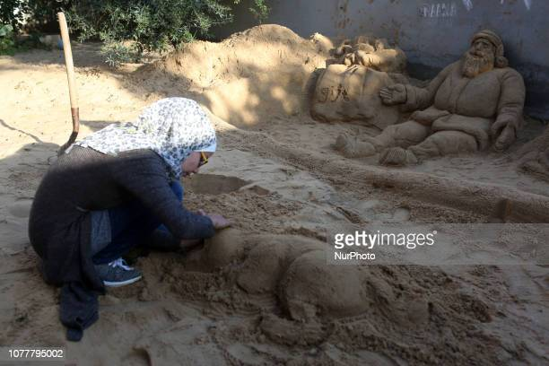 Palestinian artist Raana Ramlawi puts the final touches on a sand sculpture in Gaza city on January 5 2019