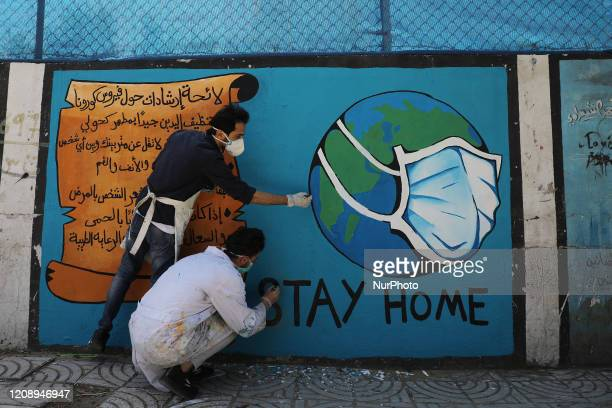 Palestinian artists draw a mural during awareness campaign about the coronavirus COVID-19, in Gaza on,City April 2,2020.