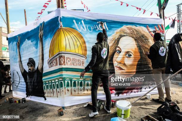 Palestinian artists paint a portrait of Ahed Tamimi 16yearold prominent campaigner against Israel's occupation and who is currently detained and...