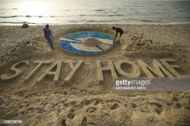 """Palestinian artists work on a sand sculpture depicting the earth with a message reading """"Stay Home"""" along a beach in Gaza City during the COVID-19..."""
