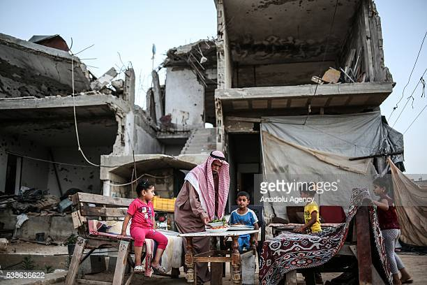 Palestinian Atif El Kura and his family break their fast at debris of their house, which was demolished after Israel's attack in 2014, in Khan Yunis...
