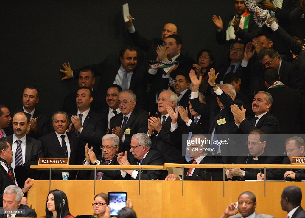 Palestinian Authority President Mahmoud Abbas (L, seated front row) and the delegation celebrate after the United Nations General Assembly voted to approve a resolution to upgrade the status of the Palestinian Authority to a nonmember observer state November 29, 2012 at UN headquarters in New York. AFP PHOTO/Stan HONDA