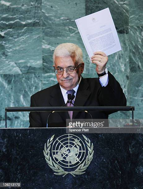Palestinian Authority President Mahmoud Abbas holds up papers for statehood while addressing the United Nations General Assembly on September 23 2011...