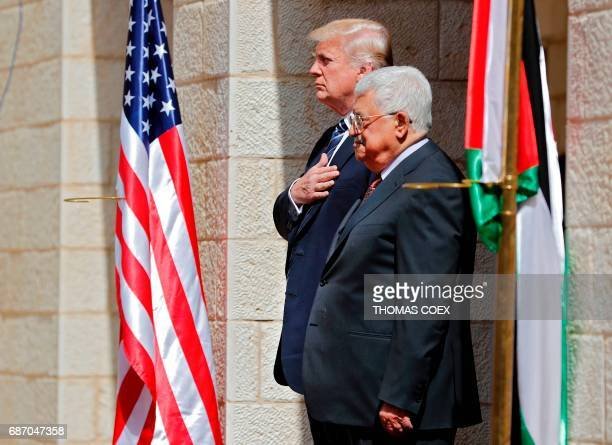 TOPSHOT Palestinian Authority President Mahmud Abbas and US President Donald Trump listen to anthems during a welcome ceremony at the Presidential...